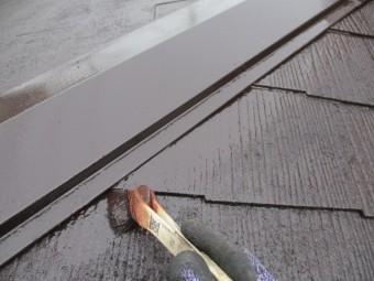 棟板金とコロニアル屋根材の取り合いを刷毛塗装中です